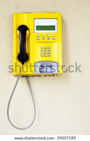 Yellow public telephone close-up on the wall - stock photo