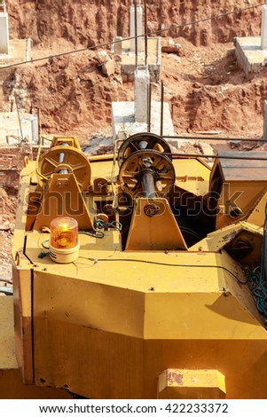 Yellow pulley of old excavator of a mobile lifting crane on a construction site background. - stock photo