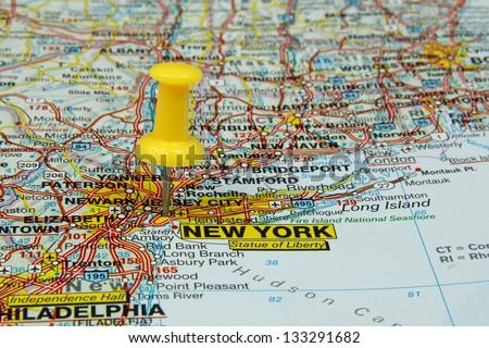 yellow push pin pointing at New York, USA - stock photo