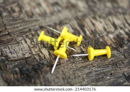 yellow push pins on old wooden background - stock photo