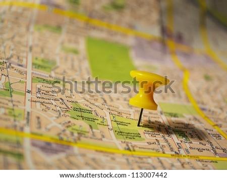 Yellow pushpin on a map - stock photo