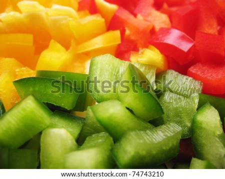 Yellow, red and green peppers Bulgarian. Slicing. Cubes - stock photo