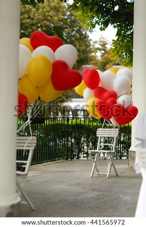 Yellow, red and white balloons with a heart shape pinned to the white garden chairs - stock photo