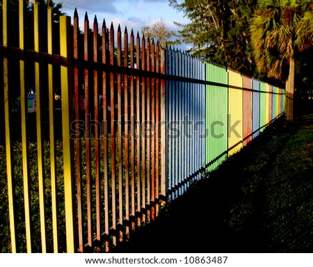 Yellow red blue green playground fence. - stock photo