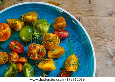 Yellow, red, green, orange tomatoes with olive oil, pepper, rock salt and sprigs of thyme on a bright blue dish, against a wooden background. - stock photo