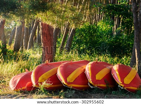 Yellow red Kayaks upside down on the river shore bank - stock photo