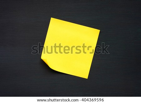 yellow reminder sticky note on black board.(blank post it note) flat lat.  - stock photo