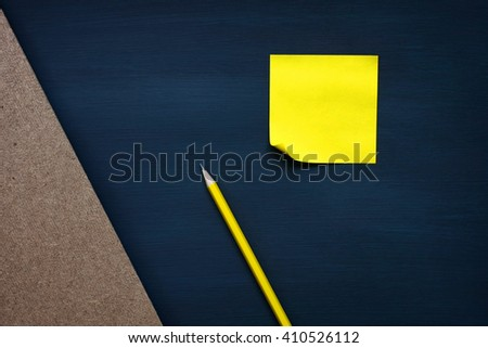 yellow reminder sticky note on black board.(blank post it note) flat lay. - stock photo