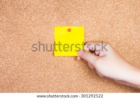yellow reminder sticky note on cork board with hand holding, empty space for text - stock photo
