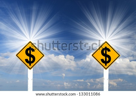 Yellow Rhombus Road Sign With Dollar Sign Inside On Blue Sky Background and Rays of Light - stock photo