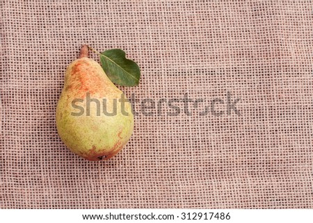 Yellow  ripe juicy pear on sacking background - stock photo