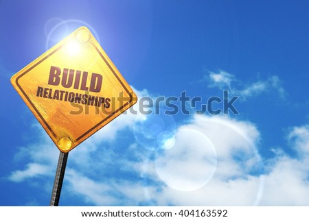 Yellow road sign with a blue sky and white clouds: build relationships - stock photo