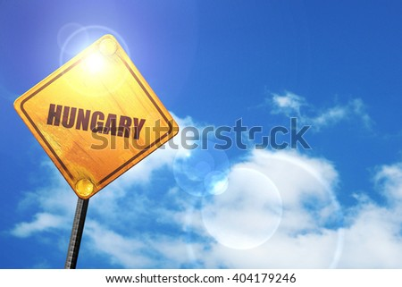 Yellow road sign with a blue sky and white clouds: Greetings fro