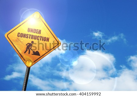 Yellow road sign with a blue sky and white clouds: Under constru - stock photo
