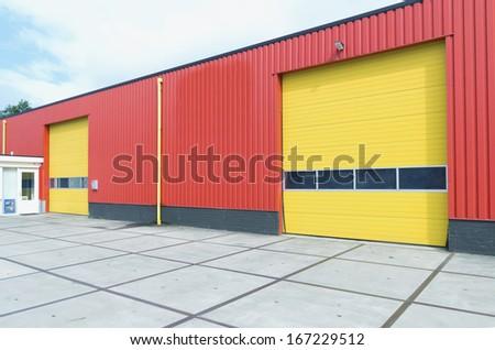 yellow roller doors in an industrial warehouse - stock photo