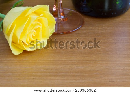 Yellow rose with a bottle of wine and a glass - stock photo