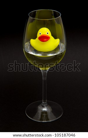 Yellow rubber duck in a wineglass with water (black background) - stock photo