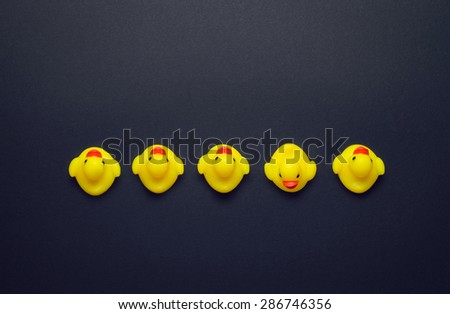 Yellow rubber ducks aligned in a line one pointing in a different direction over dark grey background, above view - stock photo