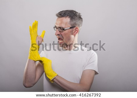 Yellow rubber glove bursting on man's hand while putting them on to clean the toilet - stock photo