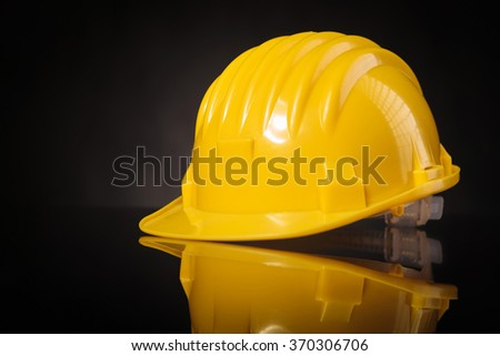 Yellow safety helmet on black reflective table, studio picture - stock photo