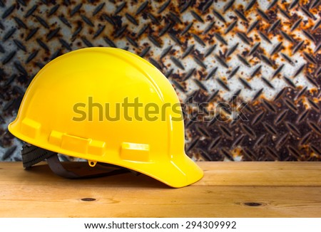 Yellow Safety Helmet on Wooden Floor with Steel Plate Grunge Background, color pop tone - stock photo