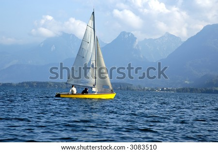 Yellow sailboat sailing on mountains lake. Wolfgangsee, Salzkammergut, Austria