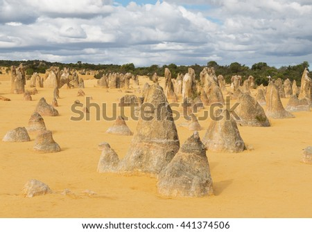 Yellow sand dunes and  limestone  pillars  Pinnacles Desert in the Nambung National Park, Western Australia.Selective focus on the front rocks. - stock photo