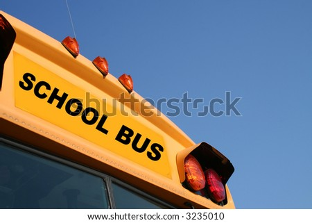 Yellow school bus against a blue sky - stock photo