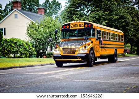 Yellow school bus driving along street - stock photo