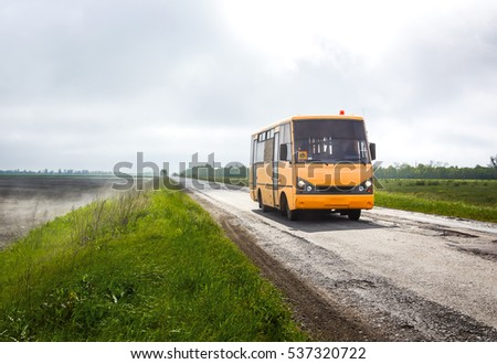 yellow school bus driving on a foggy road