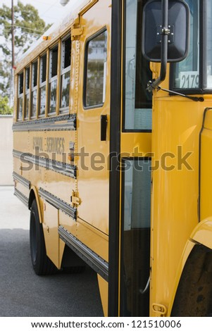 Yellow school bus in parking lot - stock photo