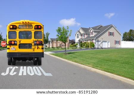Yellow School Bus on Street in Luxury Suburban Neighborhood - stock photo