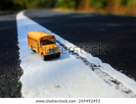 Yellow school bus toy model on country road .Shallow depth of field composition. - stock photo