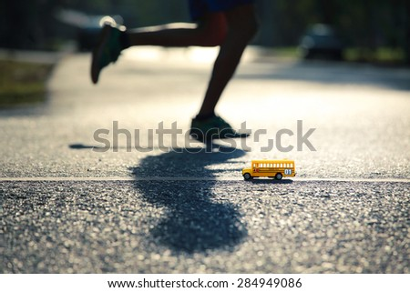 Yellow school bus toy model the road crossing and a running man.Shallow depth of field composition and  afternoon scene. - stock photo