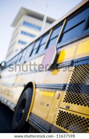 Yellow school bus with office building in background - stock photo