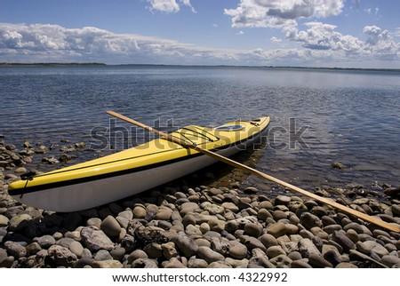 Yellow sea-kayak on beach - stock photo