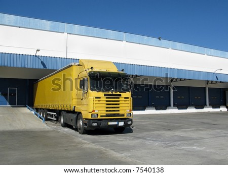 Yellow semi truck sitting at a loading dock - stock photo
