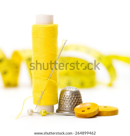 Yellow sewing accessories: thread, needle, buttons, thimble and measuring tape - stock photo