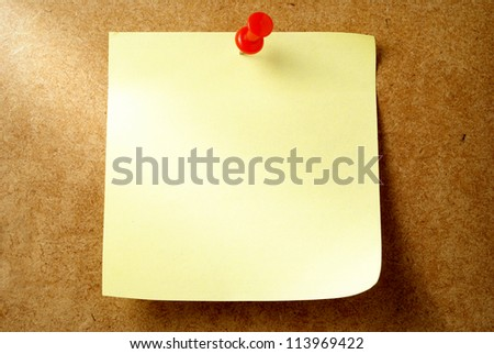 yellow sheet of paper for notes and pushpin - stock photo