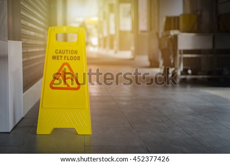 yellow sign inside building hallway,Sign showing warning of caution wet floor,selective focus,vintage color.