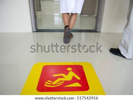Yellow sign on floor that alerts for wet floor. - stock photo