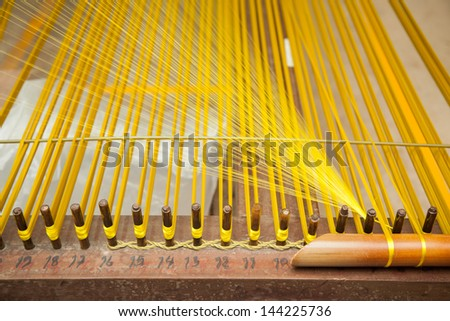 yellow silk thread on the weaving tool - stock photo