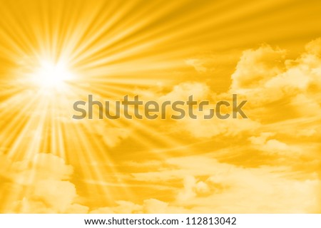 yellow sky with clouds, sun and sun rays - stock photo