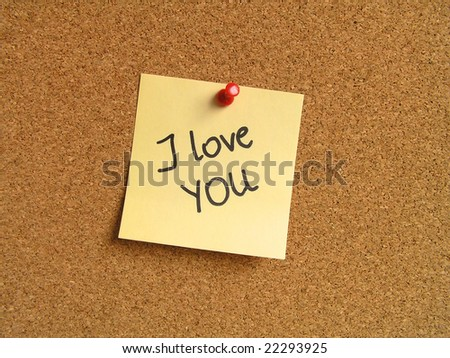 Yellow small sticky note on an office cork bulletin board. I love you confession. - stock photo