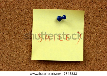 Yellow small sticky note on an office cork bulletin board. Smile! - stock photo
