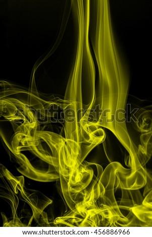 yellow smoke on black background, movement of yellow smoke - stock photo
