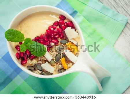 Yellow smooth with pomegranate, quinoa granola, chia seeds and dry fruits