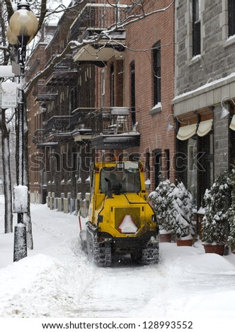 yellow snow tractor cleaning a montreal street - stock photo