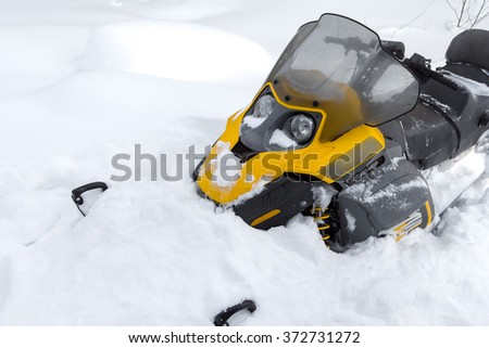 Yellow snowmobile stopped in a deep snowdrift.