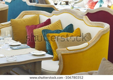 yellow sofa in a luxurious restaurant with a few colorful pillow - stock photo